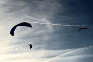 dwoje pilotów leci z paralotnią na tle nieba