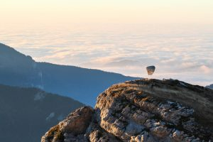 człowiek startuje z paralotnią na szczycie góry